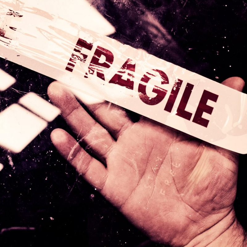 A hand is seen in front of a glass pane with the words 'Fragile' in red writing