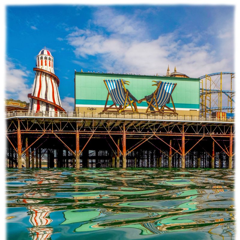 brighton pier the heater scelter and reflections of the pier on a calm sea