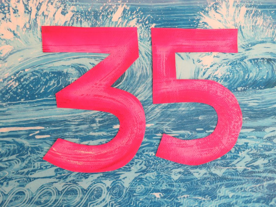 Turquoise waves created on fabric using hot wax and dyes. The numbers 35 in bright pink and red on top.