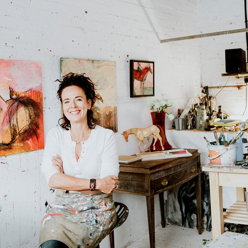 female artist sitting in her white studio which is an old cowshed in front of her colourful abstract horse paintings