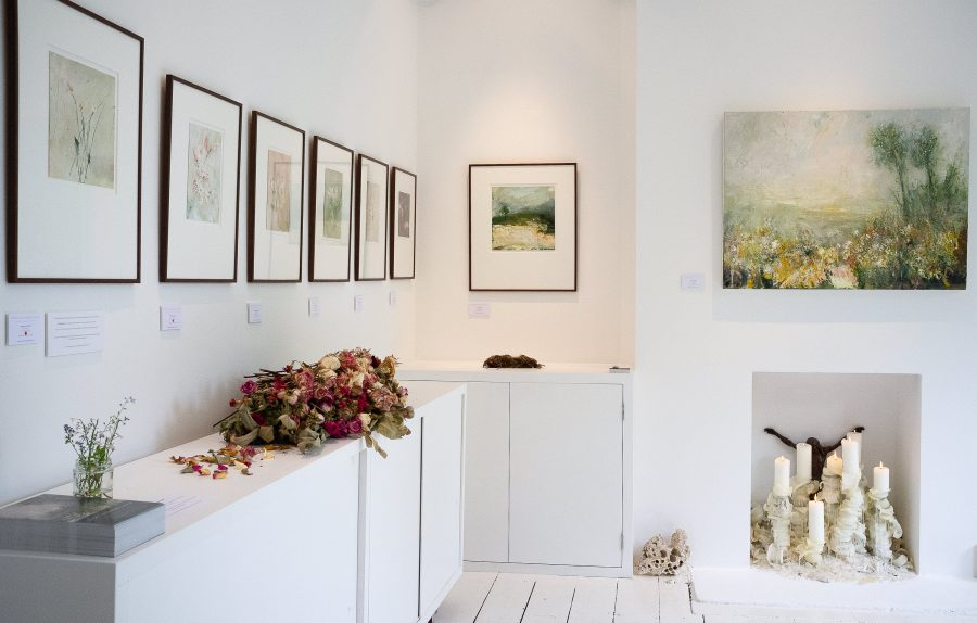 Exhibition of paintings hanging in a contemporary white living space
