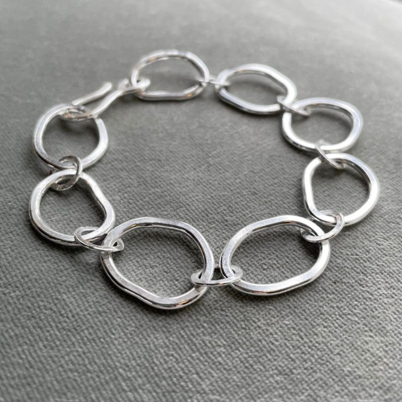 Organically shaped, flattened link Sterling Silver bracelet closed with a hook clasp.
