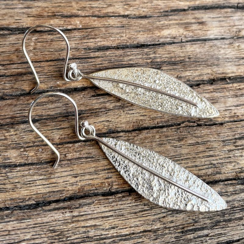 Asymmetric leaf earrings with a shiny, rustic surface texture and central vein. Hook fixing.