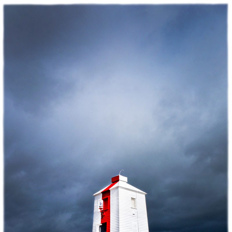 A white wooden lighthouse on stilts on a sandy beach with stormy skies and the sea behind