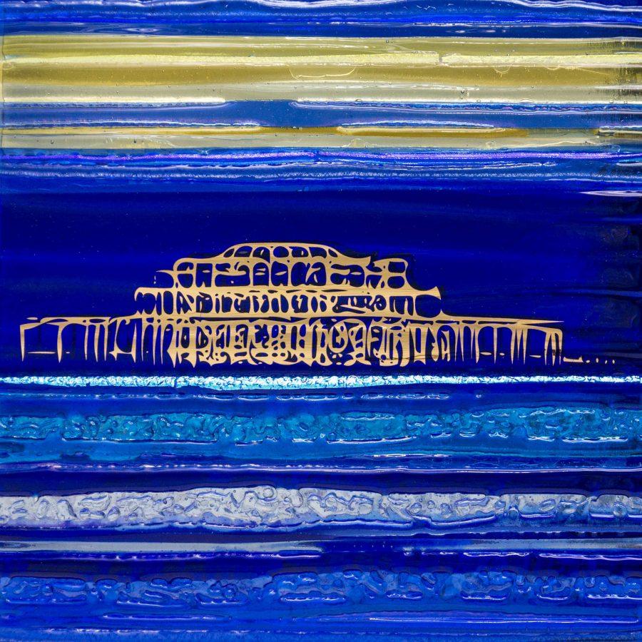 A textured Glass Tile in blue and yellow glass with an abstract image of the west pier in shiny 22ct gold