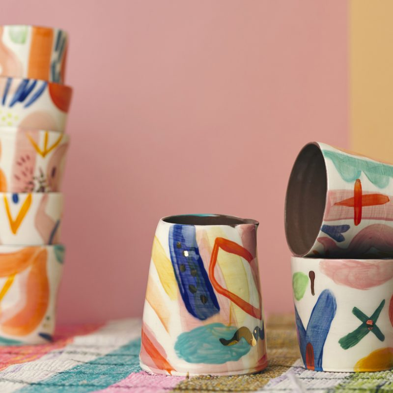 6 handpainted colourfully painted drinking vessels and one jug, all made in terracotta. the vessels are set on a stripy pink and green blanket and a backdrop of bubblegum pink card.