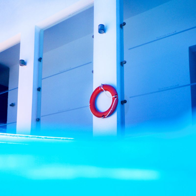 underwater blue of a swimming pool with a red life belt