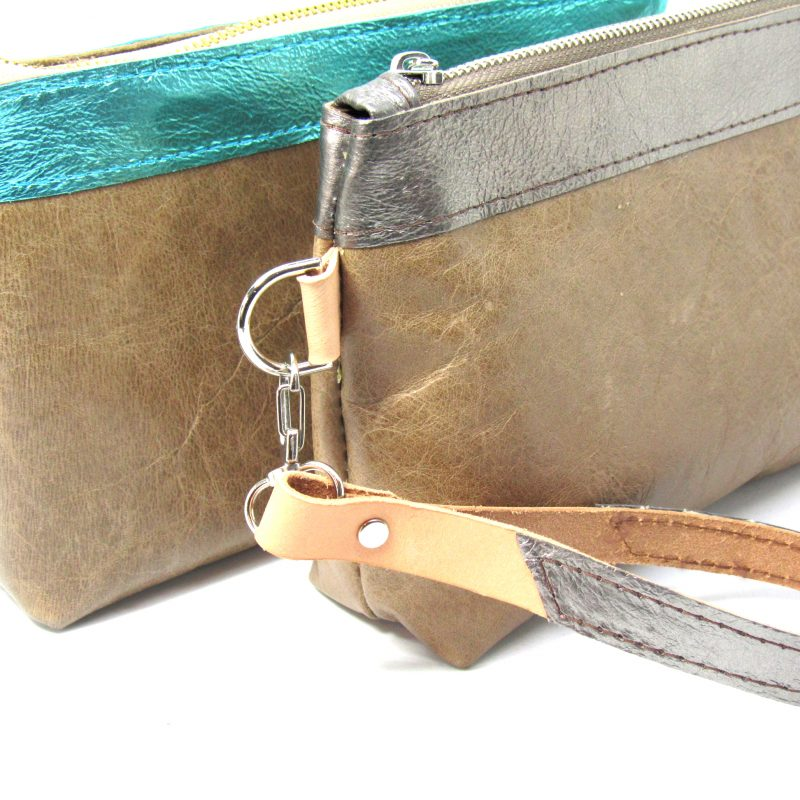 Small brown and turquoise leather bag with zip closure and wrist strap.