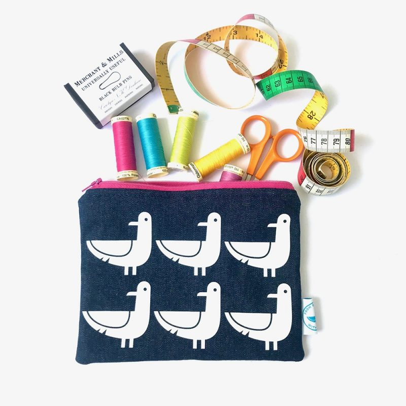 """Zipped pouch in denim fabric with """"Oscar the Seagull"""" print on the front. Available with contrasting zip and lining in either pink, turquoise or orange. Also available in a small size."""