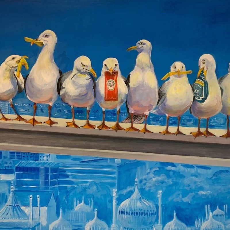 """The larger """"Who Forgot The Fish?"""" image is loosely based on the famous """"Lunch Atop a Skyscraper"""" photograph by C B Ebbetts. Instead of builders eating their lunch on a construction beam overlooking Manhattan, this shows our quirky seagulls sharing chips and sauces, overlooking Brighton."""