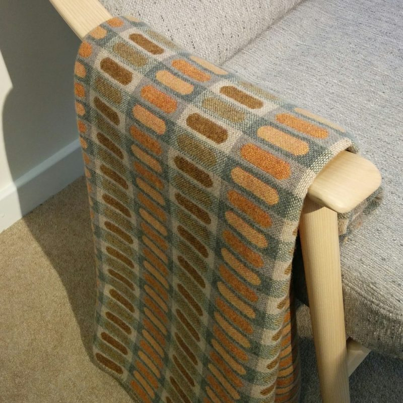 The demi has soft curved motifs and the saffron colourway is a blend of apricot, ochre and light greys. The photo shows it draped over the wooden arm of a mid century chair.