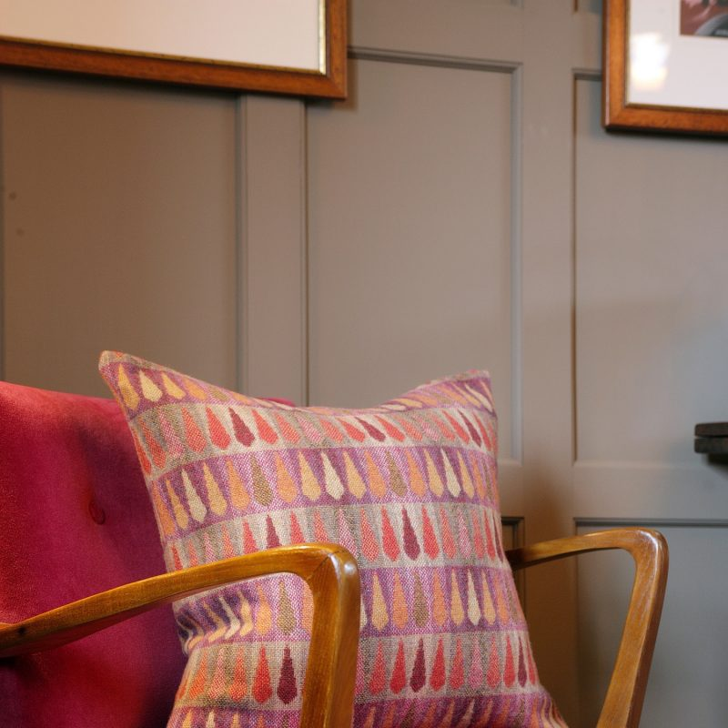 A Fern Berry cushion in soft merino wool. Colours are pinks through to oranges as well as muted green. The photo shows it on a bright pink velvet chair.