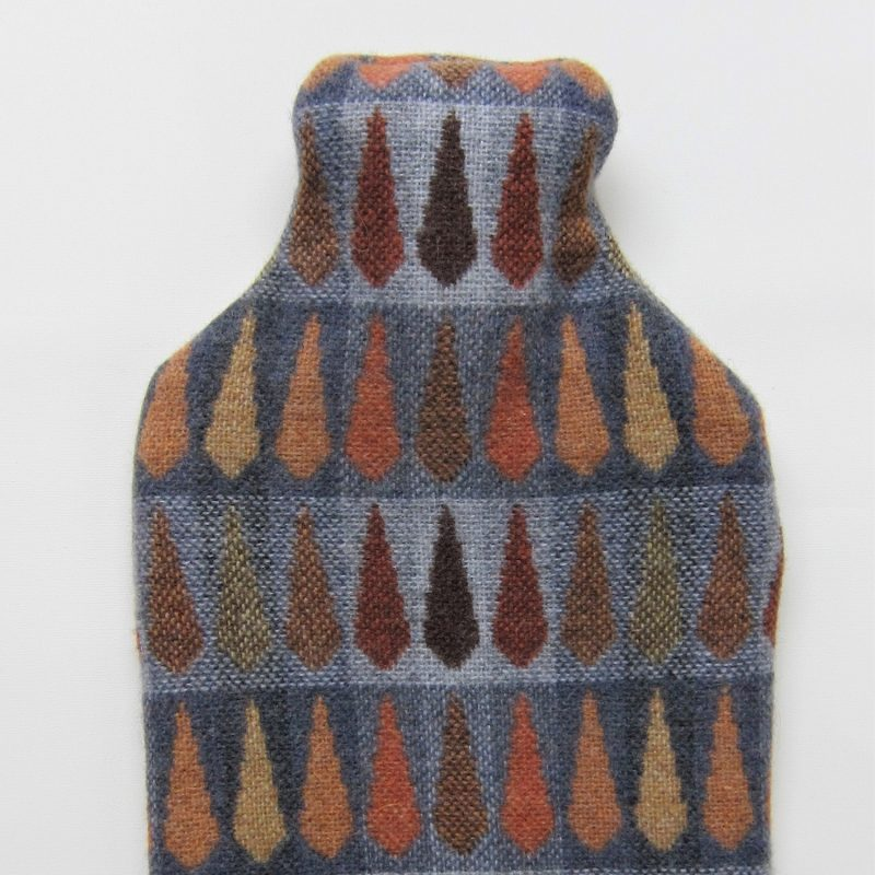 A hot water bottle with a cover-- in this case our Fern Copper fabric, gradating coppers tones and greys.