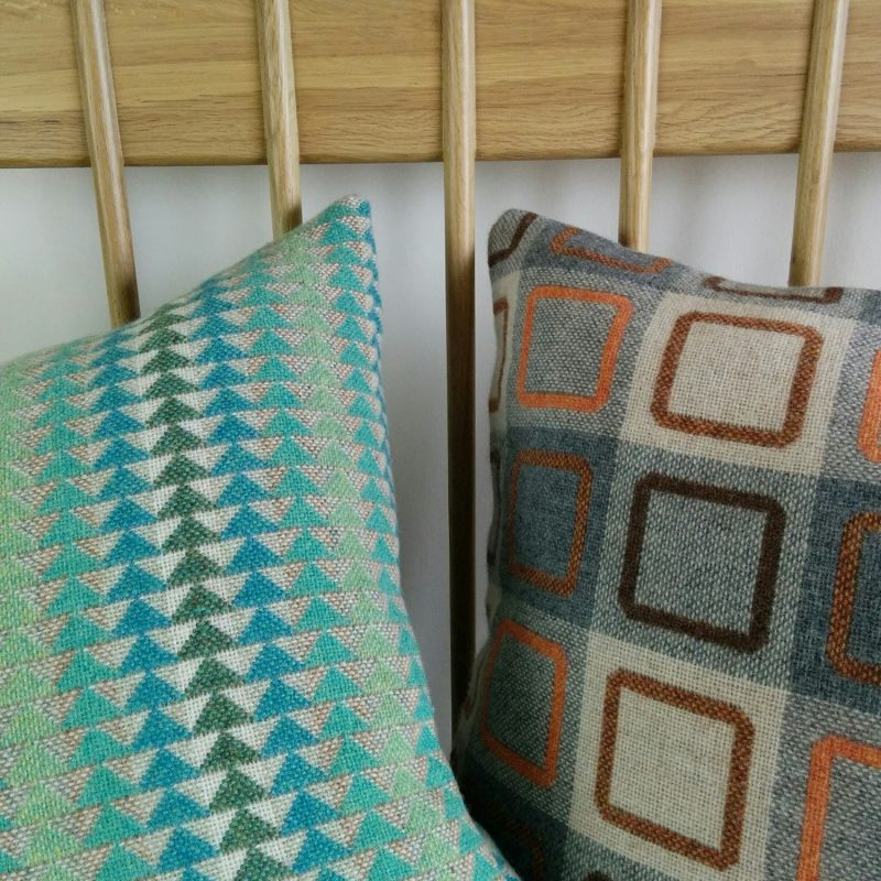 Two cushions. Oneis in Jig Mint fabric--tiny triangles, tonally gradating, the other is a plaid design --squares with rounded edges--Squircle Outline.