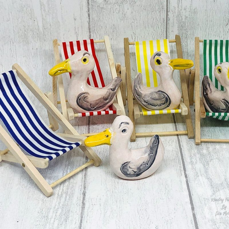 Miniature Seagulls Sitting On Their Own Mini Deck Chairs. The Deck Chairs Are Available In Yellow And White, Green And White, Red And White And Yellow And White.