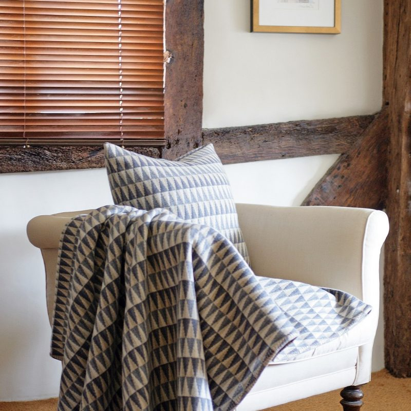 A Prism grey throw and cushion on a chair in a cottage in Sussex. Prism is a geometric all-over design.