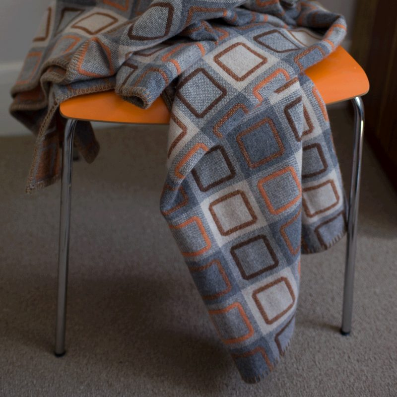 The Squircle Outline Orange throw on an orange chair