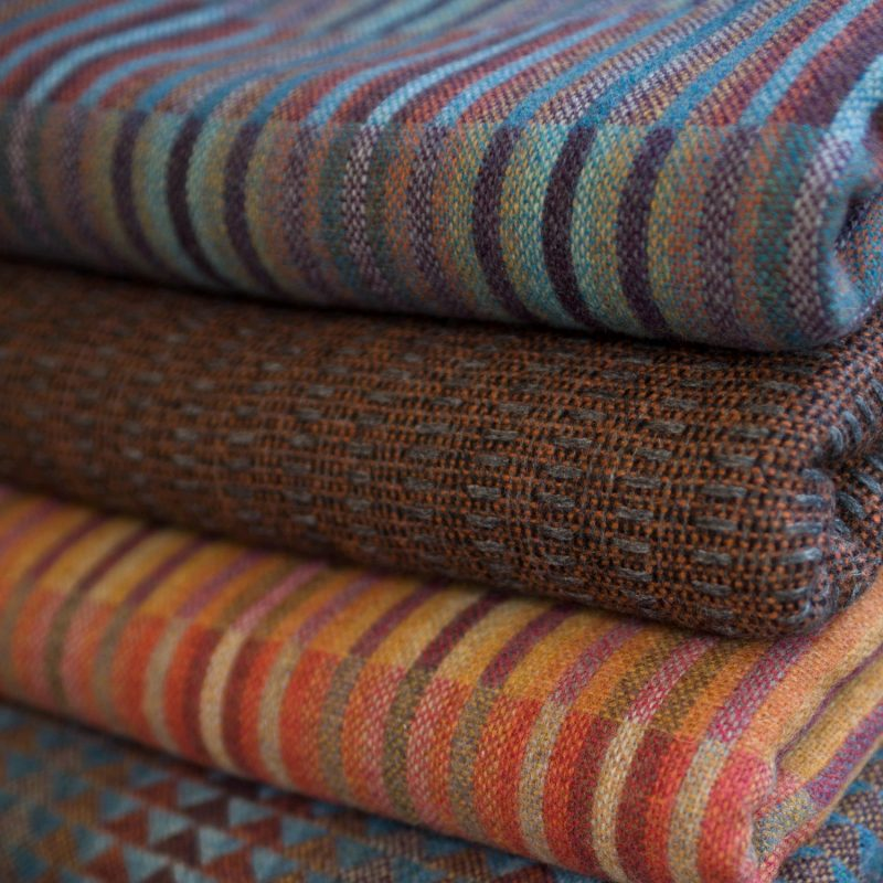 A pile of woven throws in mostly warm colours: reds. oranges, maroon and blue.