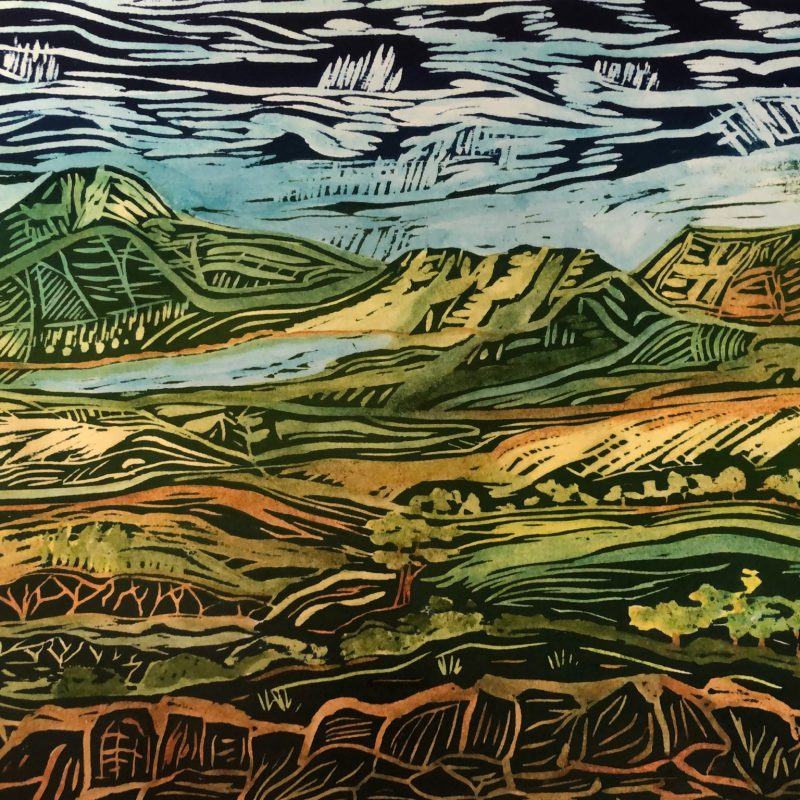 Wood relief capturing hills and valleys. Greens and blues. You can see the carving marks.
