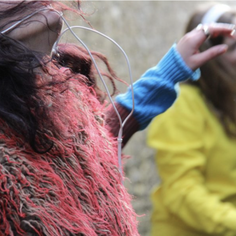 Two women dancing with headphones on, one with a red fluffy jacket, the other in a bright yellow jumper
