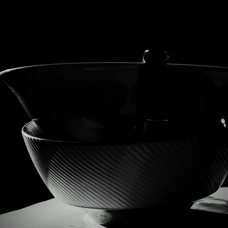 Close up black and white photo of bowls in shadow