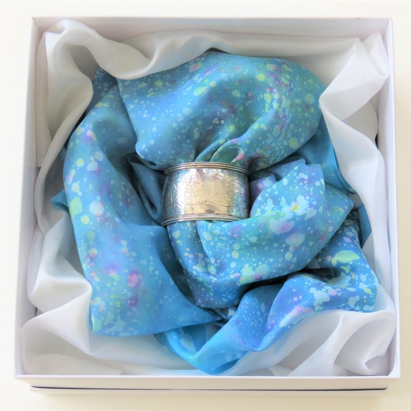 Square white box (19cms. x 19cms.) with antique engraved silver napkin ring and a batik multi-coloured square silk scarf