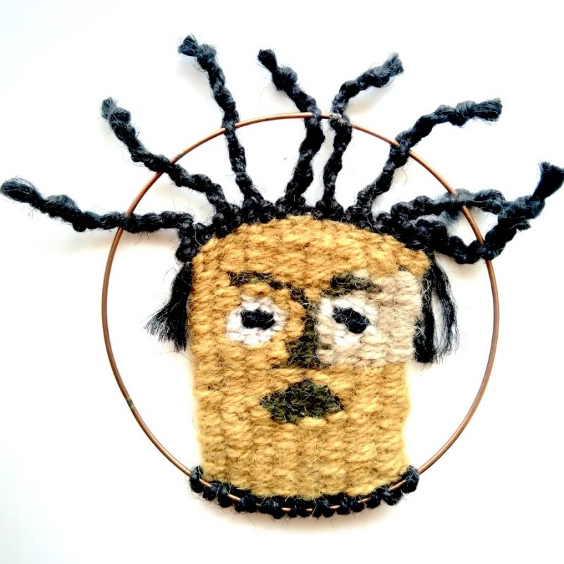 Handwoven face with a worried expression and knotted hair, mounted on a copper hoop
