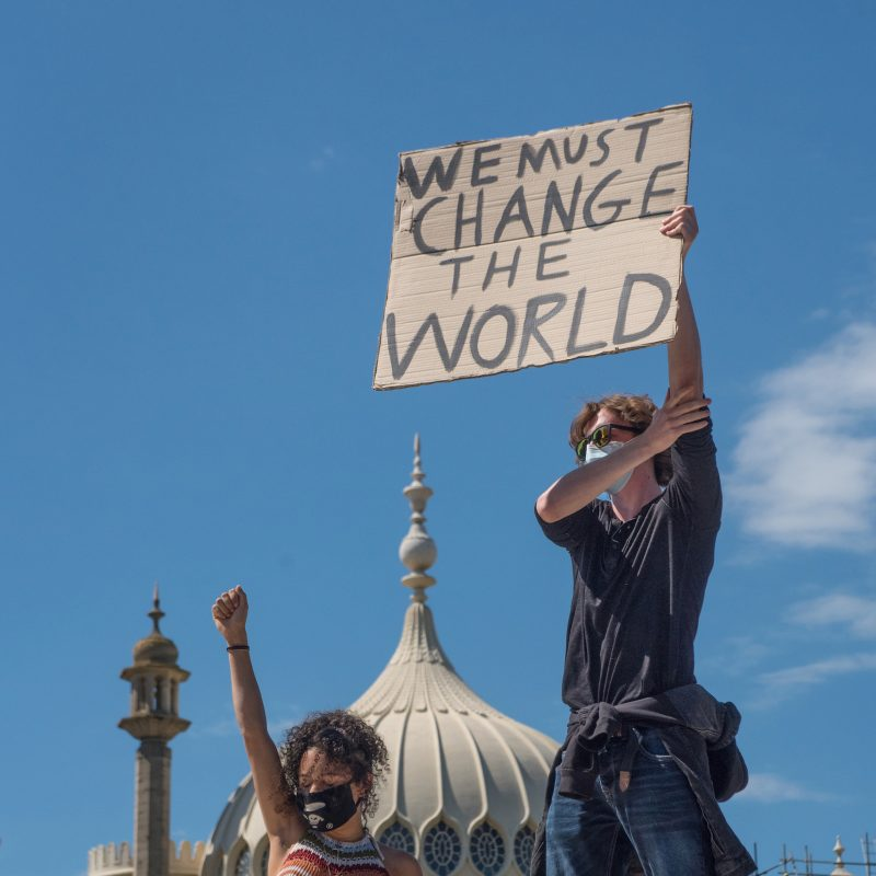 Photo of  two people holding a banner up saying We must change the world
