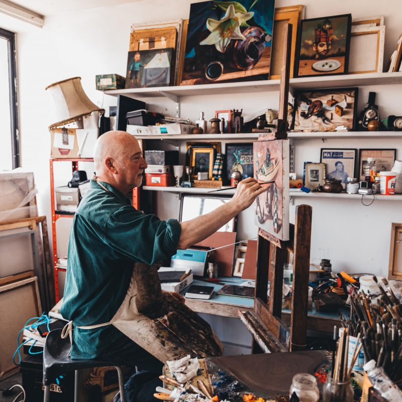 Artist in studio, sat painting at a canvas. In front of shelf filled with objects, canvases and paints.