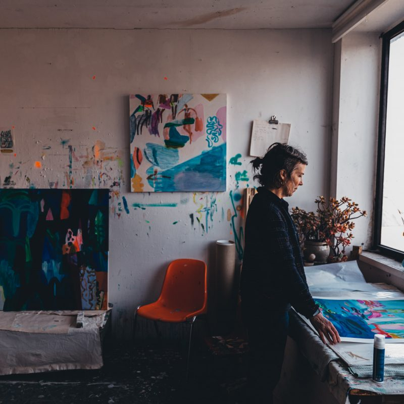 Artist in studio space, facing light-filled window and browsing through work on desk. Colourful, abstract paintings on the wall and on the desk.