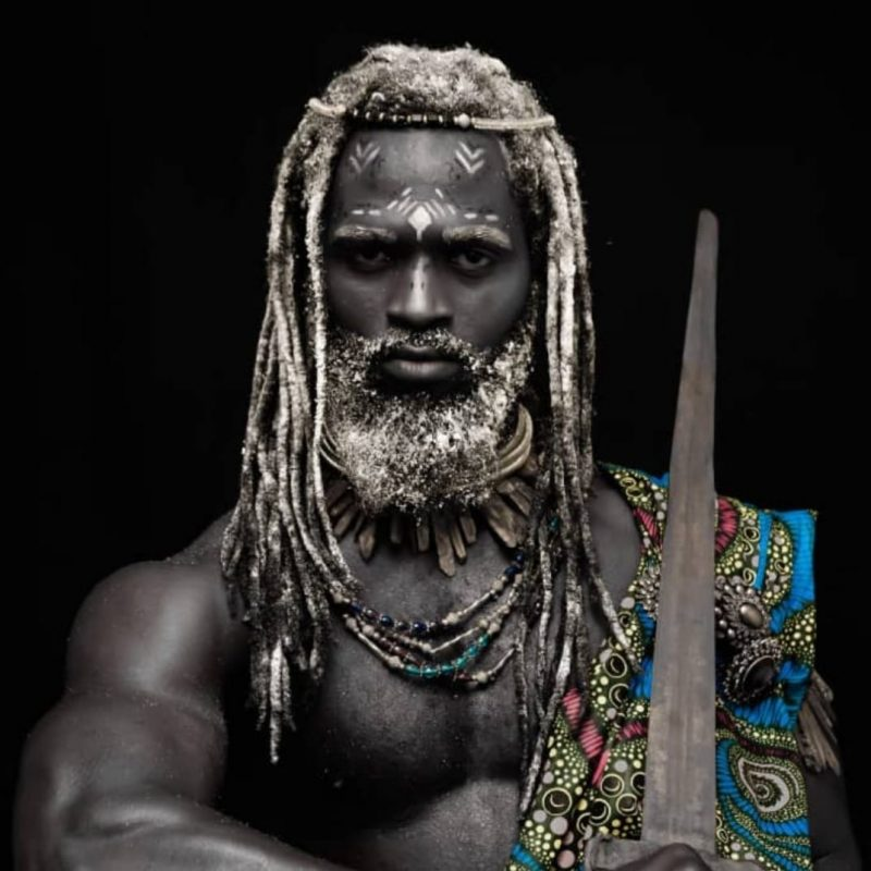 Black and white augmented - A lookalike Zeus with dark skin and white dread locks. His robe is in wax and he poses as a warrior