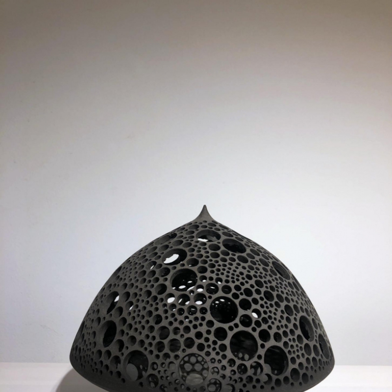 Black sculpture in ceramic perforated with holes