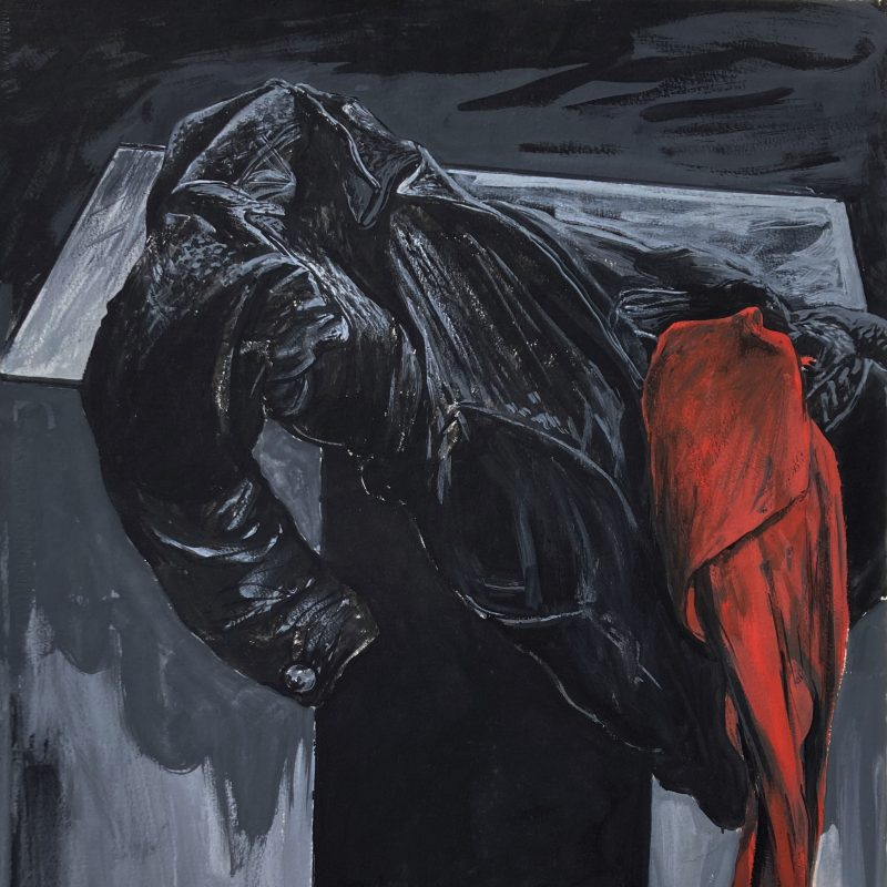 A black and well worn leather jacket is shown draped over a black box with a scarf of deep red cascades out of one of the  pockets. There is a presence and weight to the objects - the red of the scarf contrasting against the blacks and greys of the other objects.
