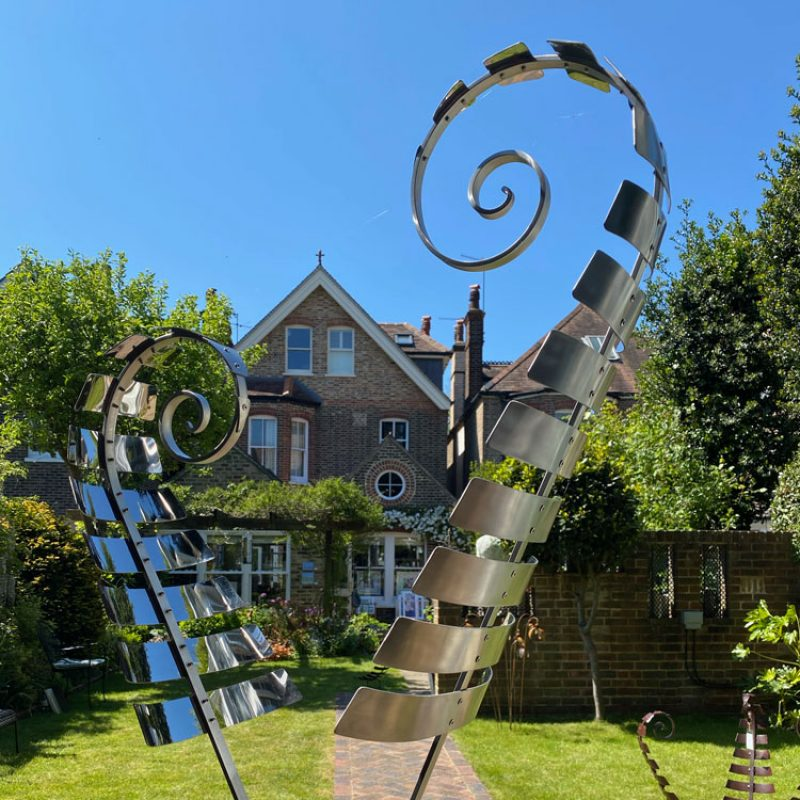 The Art in Bloom House viewed through the sahpes of a fern sculpture