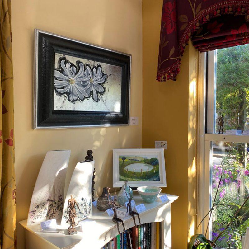An arrangement of art in the corner of the Garden Room at Art in Bloom