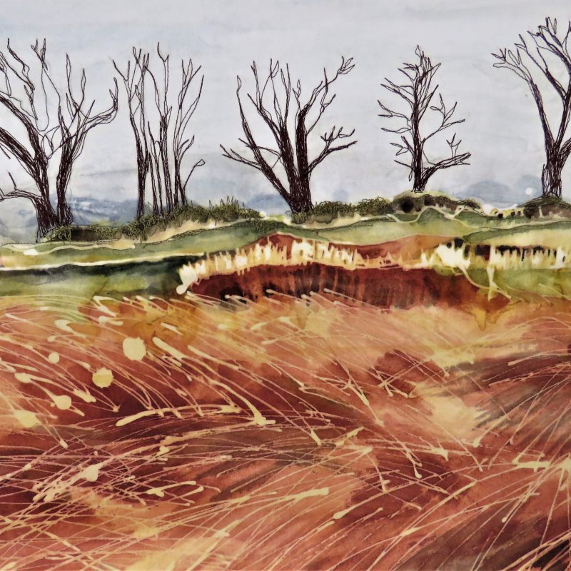 Landscape batik with grey sky ,orange and yellow windswept field in foreground, bare trees embroidered in distance.