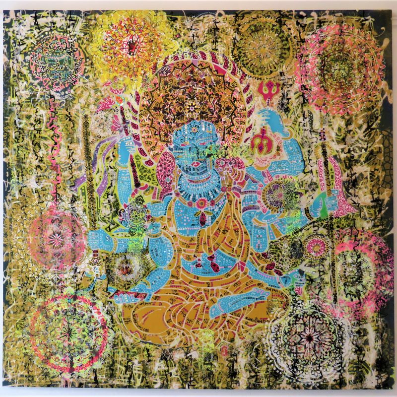 Large batik of an Indian style god. Complex patterns in yellows, oranges and black.                                       sparkling sequins attached which look like jewels.