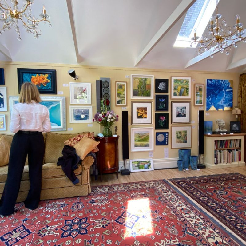 A wall of paintings and prints on display in the garden room at Art in Bloom